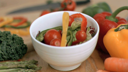 Tomatoes dropping in super slow motion into salad Footage