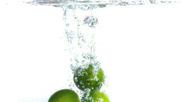 Limes falling into water in super slow motion Footage