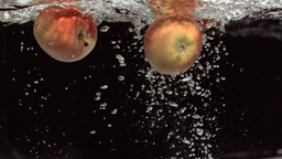 Apples moving underwater in super slow motion Footage