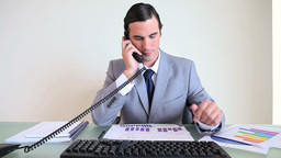 Businessman working while picking up the phone Footage