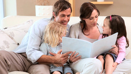 Smiling family reading a book together Footage