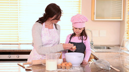 Mother helping her daughter to cook Footage