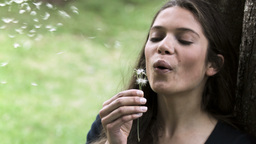 Relaxed woman in slow motion blowing a dandelion Footage