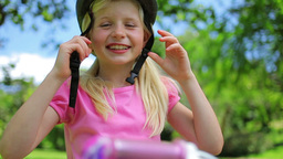 Girl puts on a pink cycling helmet and fastens the Footage