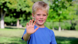 Boy waving towards the camera while smiling Footage