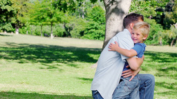 Father kneels on the grass before hugging his son  Footage