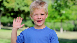 Boy smiling and waving before giving the thumbs up Footage