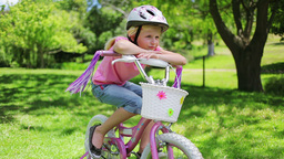 A girl sits on a bike while leaning on the handleb Footage