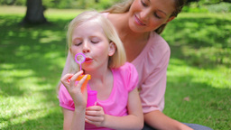 A girl repeatedly blows bubbles with her mother as Footage