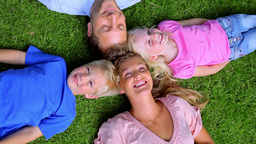 Overhead shot of a family smiling as they lie head to head in grass Live Action