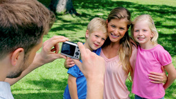 A man takes a photo of his family who are embracin Footage