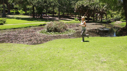 A woman runs in the park as the camera follows her Footage