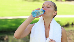 A woman walks in the park and takes a drink as she Footage