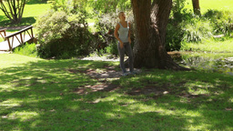 A woman jogs in the park as she stops by a tree an Footage