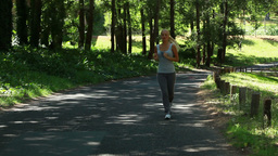 A woman jogs in the park and then is jogging on a  Footage