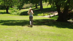 A woman jogs in the park away from the camera Footage