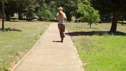 Jogging woman runs down the footpath Footage