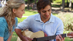 A boyfriend plays guitar for his girlfriend as the Footage