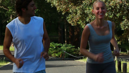 A smiling couple look to one another as they jog Footage