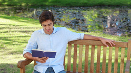 Man sits on a bench while reading a book Footage