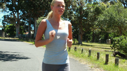 A woman wipes her head as she jogs towards the cam Footage