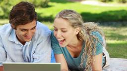 Woman lies down beside her boyfriend as they watch Footage