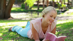 A woman lies down in the park reading as she then  Footage