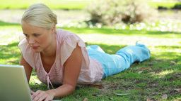 A camera pans past a woman lying down and using he Footage