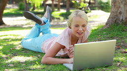 A woman lies in the park with her laptop as she la Footage