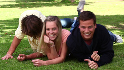 Woman laughing while lying on the grass before her Footage