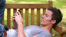 Man lies on a bench while looking at at his mobile phone before laughing and looking at camera Live Action