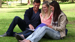 Three friends laughing as they read a book togethe Footage