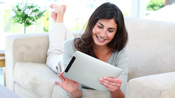 Woman using her tablet while smiling Footage