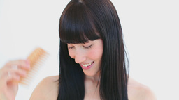 Happy woman combing her hair while laughing Footage