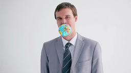 Happy executive holding a globe with his mouth Footage