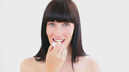 Smiling woman applying lip balm on her lips Live Action