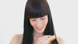 Smiling brunette using a comb Footage