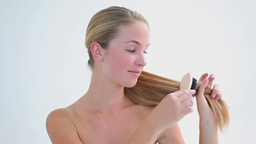 Smiling woman brushing her fair hair Footage