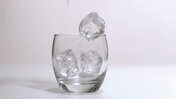 Ice cubes falling in super slow motion in a glass Footage