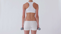 Rear view of a woman using dumbbells Live Action