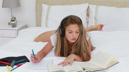 Young woman listening to music while doing her homework Footage