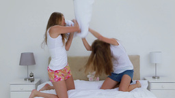 Friends in nightwear fighting with pillows Footage