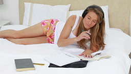 Young brunette woman studying while listening to m Footage