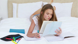 Serious young woman studying while lying Footage