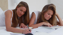 Happy young woman doing her homework with a friend Footage