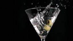 Olive skewer falling in super slow motion in a gla Footage
