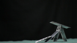 Pyramid of cards collapsing in super slow motion Live Action