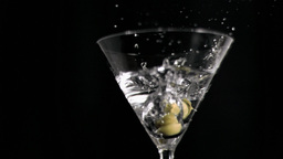 Olives in super slow motion falling in a martini Footage