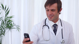 Smiling doctor sending a text message Live Action