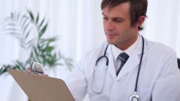 Goodlooking doctor writing on a clipboard ライブ動画